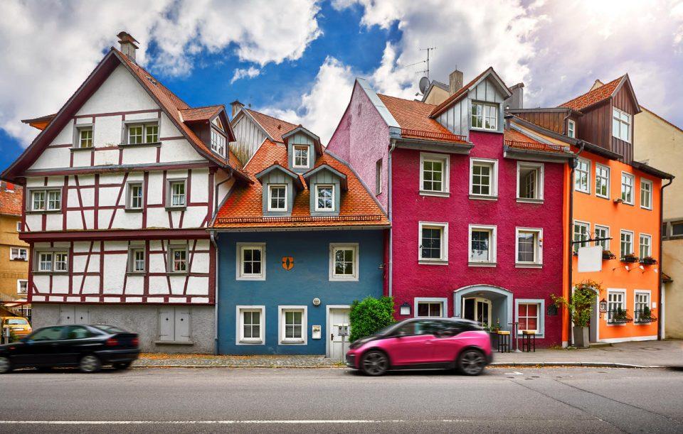 Lindau, cidade velha no lago Constance, Baviera, Alemanha. Casas bávaras alemãs tradicionais coloridas ao longo da rua com carros. Paisagem urbana de dia com arquitetura azul céu e nuvens.