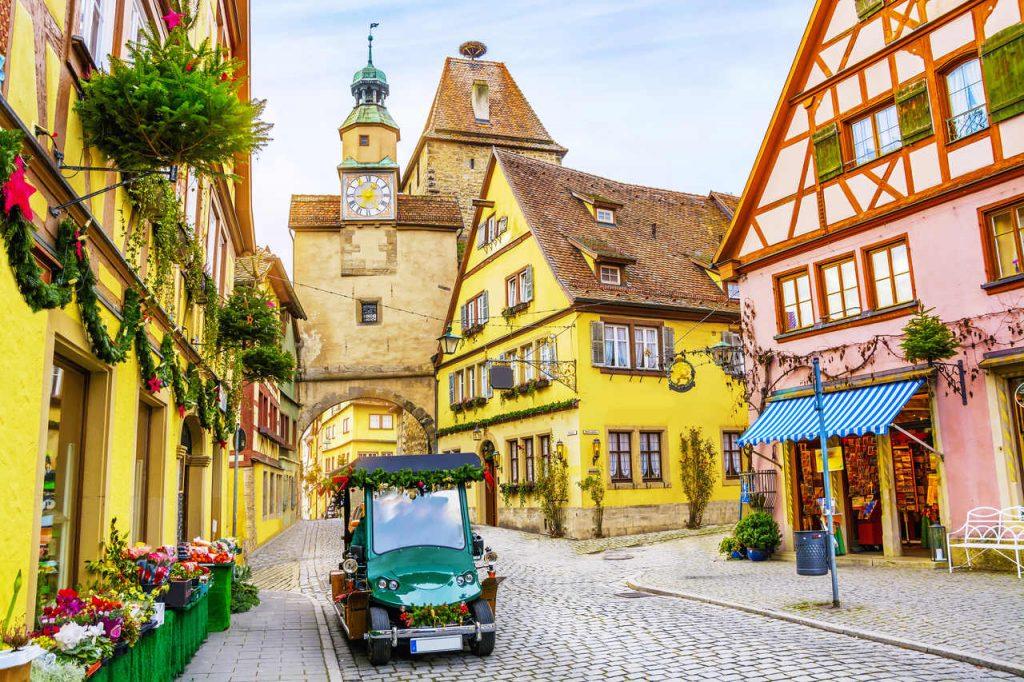 Carro retrô turístico na rua pitoresca, decorado para férias de Natal em Rothenburg ob der Tauber, cidade histórica medieval na Baviera, Alemanha.