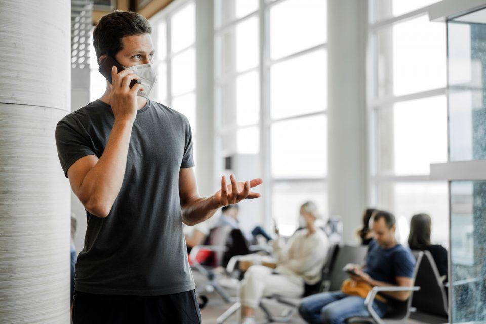 Homem com máscara respiratória está esperando o próximo avião no aeroporto e usando telefone celular. Conceito de Coronavírus COVID-19.
