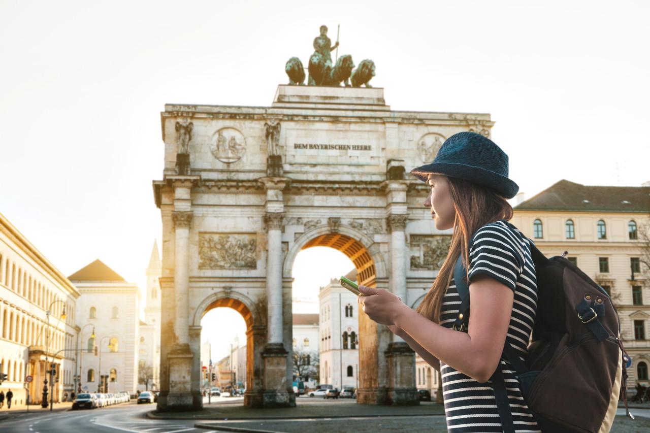 Uma garota turística com uma mochila olha para as vistas em Munique, na Alemanha. Passa pelo arco triunfal.