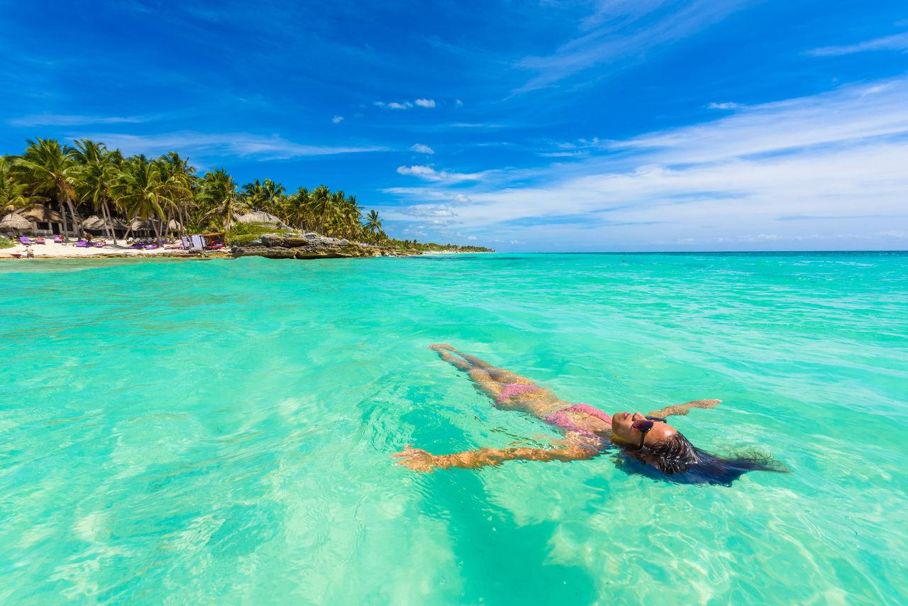Jovem relaxando em águas azul-turquesa do Mar do Caribe em frente à praia paradisíaca em Tulum, perto de Cancun, Riviera Maya, México